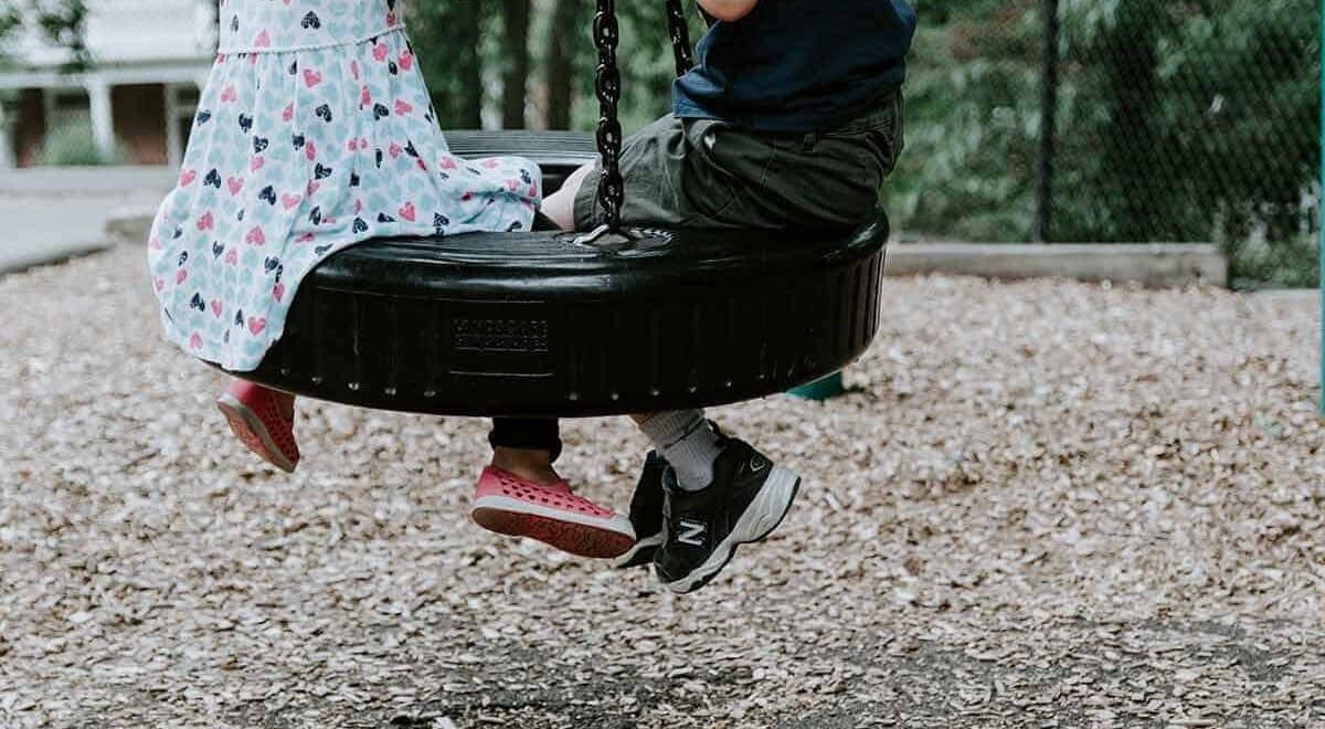 Ein Junge und ein Mädchen sitzen in einer Reifenschaukel.