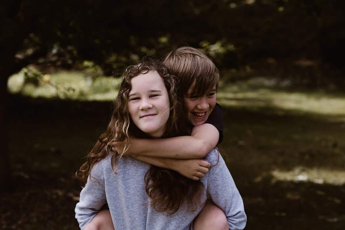 Eine junge Frau trägt einen Jungen auf dem Rücken.