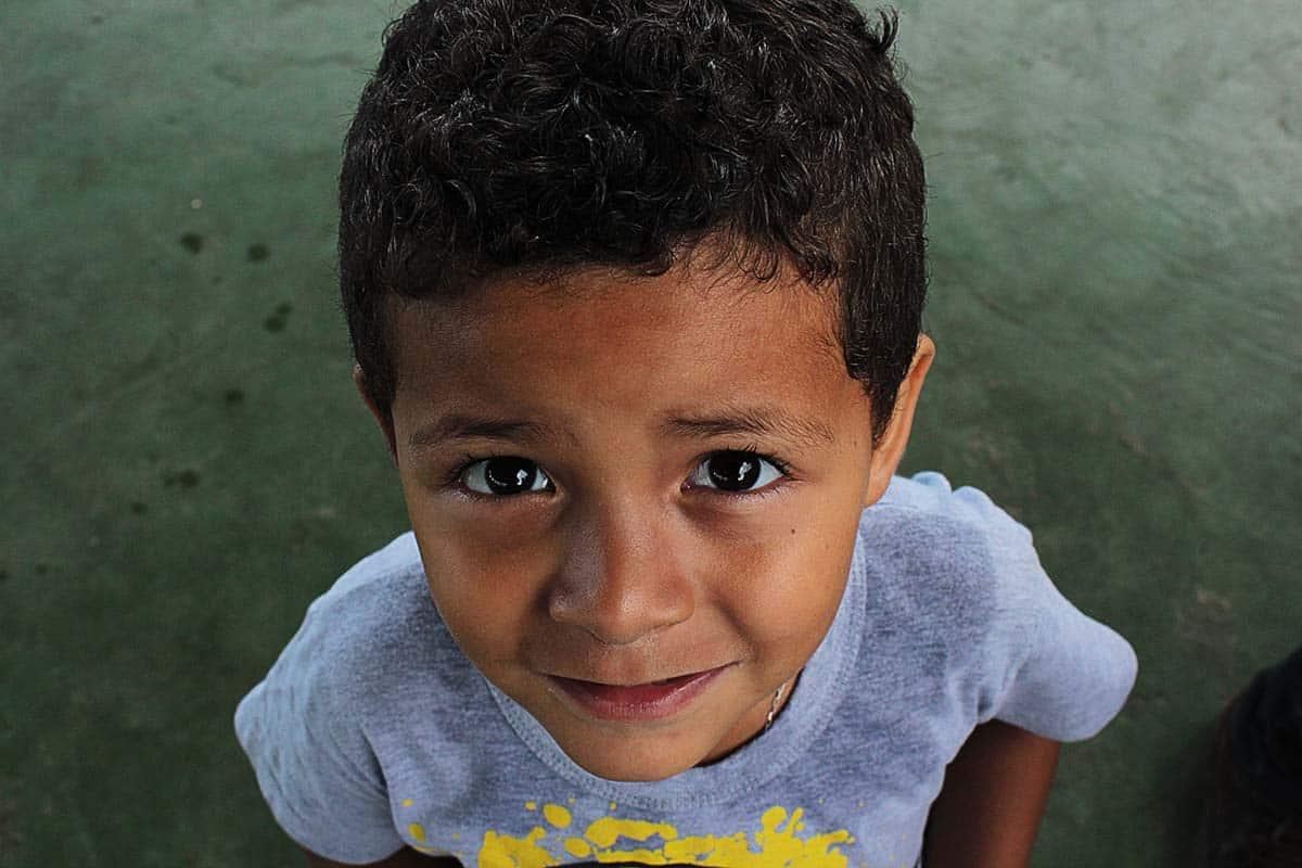 Ein kleiner Junge mit einem grauen T-Shirt schaut in die Kamera.