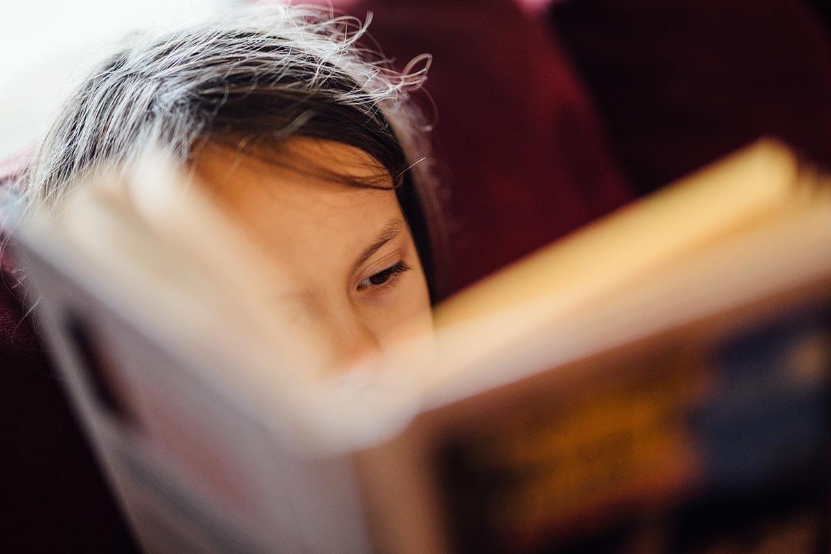 Ein Mädchen liest in einem Buch.