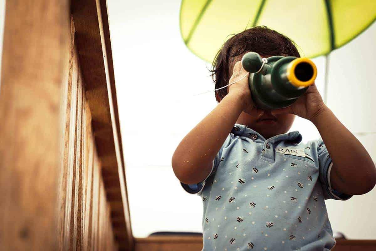 Ein kleiner Junge schaut durch ein grünes Fernglas.