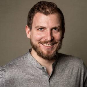 Mann mit braunen Haaren und einem braunen Bart. Er trägt ein graues T-Shirt.