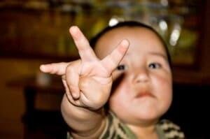 Ein kleines Kind hält seine Finger in die Kamera.