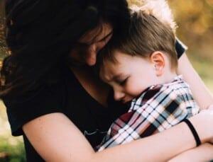 Eine Frau hält einen kleinen Jungen in den Armen.