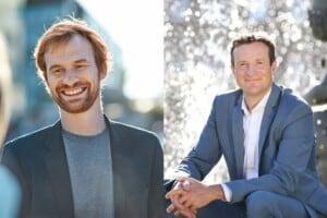 Links ist ein Mann mit roten Haaren und einem rötlichen Bart. Er trägt ein Jacket und ein graues T-Shirt. Rechts ist ein Mann mit braunen Haaren. Er trägt einen blauen Anzug und ein weißes Hemd.