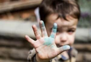 Ein kleiner Junge hält eine Hand in die Kamera. An der Hand ist blaue Farbe.