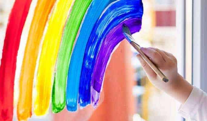 Eine Hand malt mit einem Pinsel einen Regenbogen an das Glas.