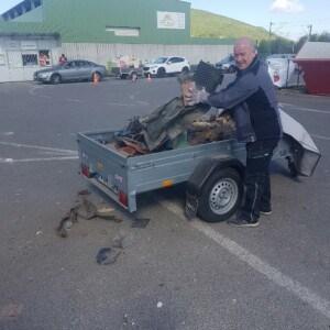 Ein Mann holt Müll aus einem vollen Anhänger. Er steht auf einem Parkplatz. Im Hintergrund sind weitere Autos zu sehen.