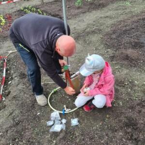 Ein Mann arbeitet mit einem Mädchen an einer Pumpe.