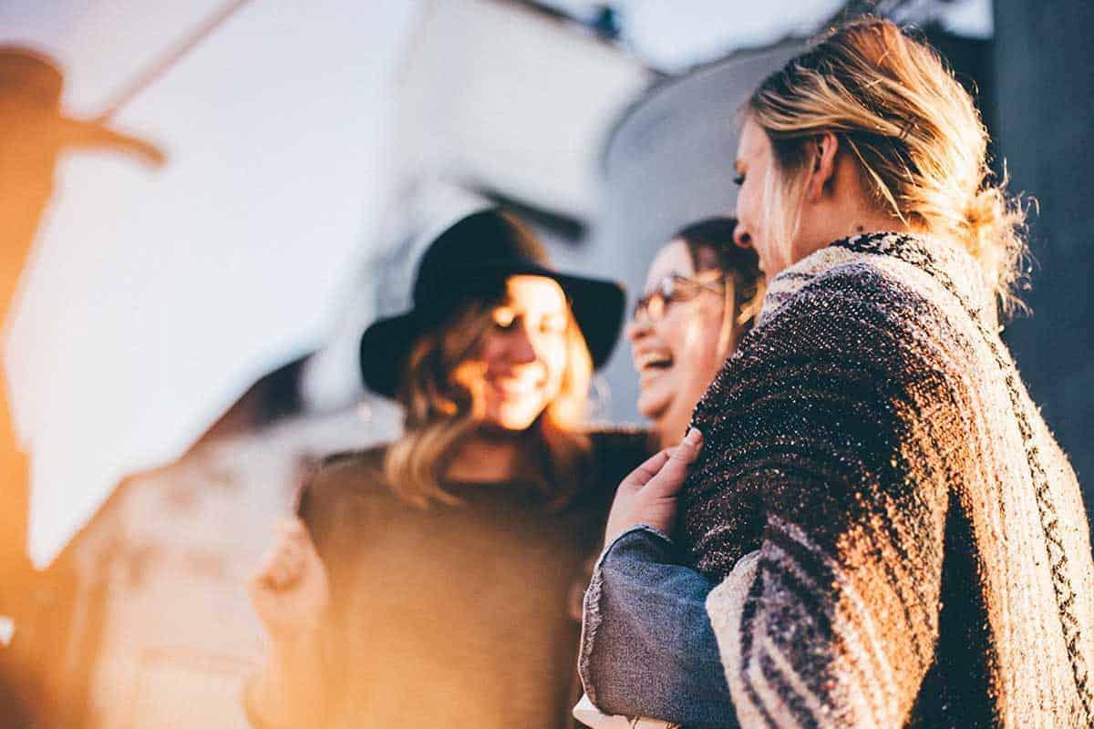 Drei Frauen steht in einem Halbkreis und lachen.