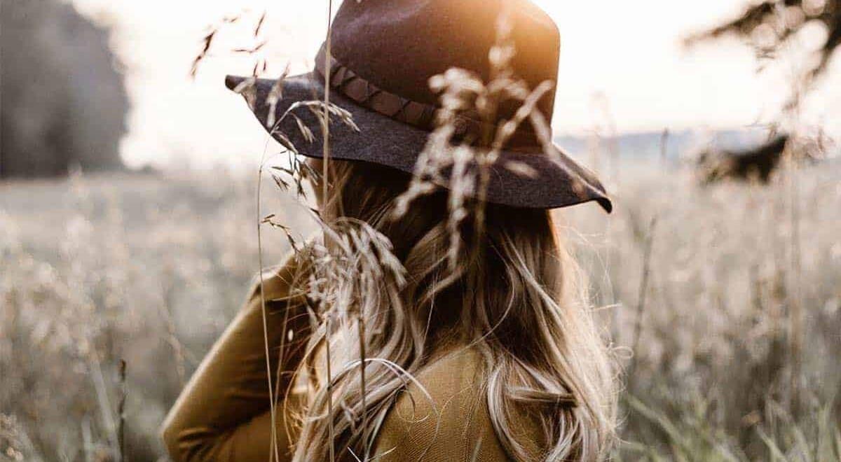 Eine Frau mit einem Hut steht in einem Feld mit hohen Gräsern.