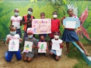 Neun Kinder stehen vor einer grüner Wand. Die Kinder halten Blätter mit einem Tannenbaum. Dahinter halten Kinder ein rosa Plakat, auf dem steht: Muchas Gracias Element-i.