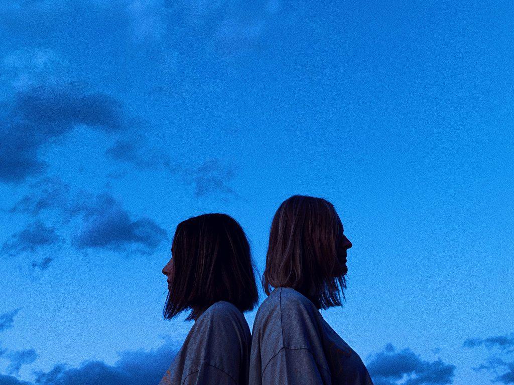 Zwei junge Frauen stehen Rücken an Rücken. Über ihnen sieht man einen blauen Himmel mit Wolken.