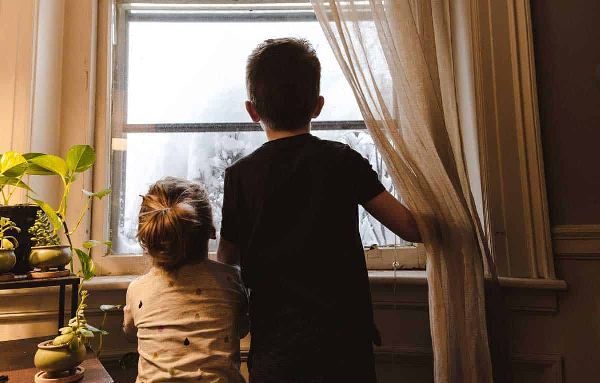 Ein Junge und ein Mädchen schauen aus dem Fenster.
