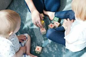 Zwei Kinder und eine Pädagogin sitzen auf einem Teppich und spielen mit bemalten Holzwürfeln.