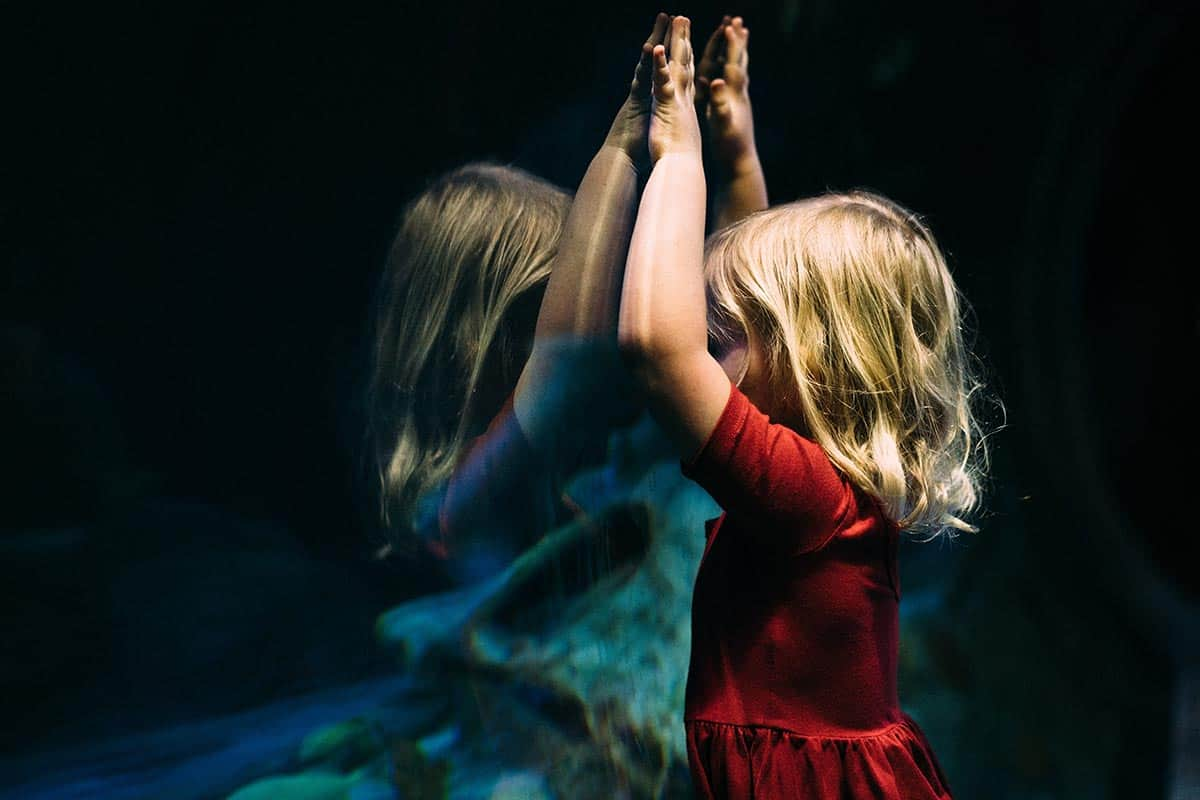 Ein Mädchen mit blonden Haaren und im roten Kleid hält die Hände nach oben an ein Aquariumsglas. Das Mädchen spiegelt sich im Glas.