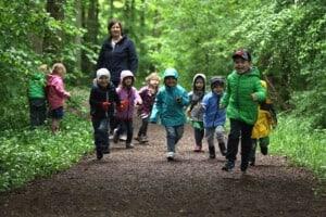 Viele Kinder laufen auf einem Waldweg. Hinter den Kindern steht eine Pädagogin.