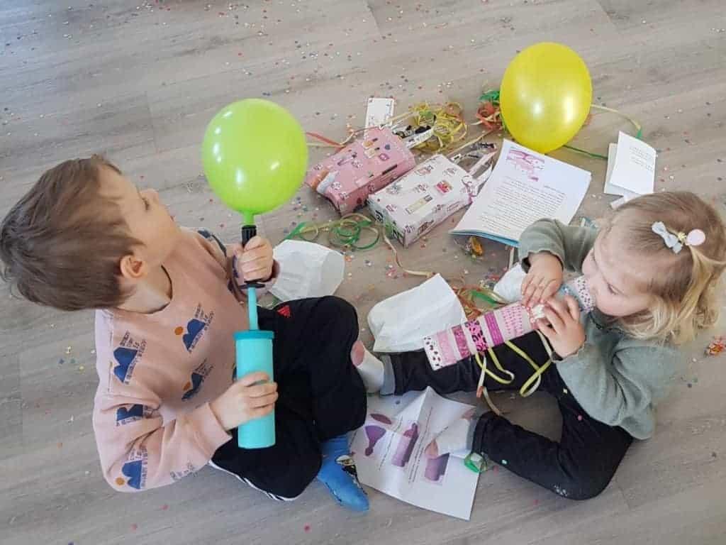 Ein Junge sitzt auf dem Boden und bläst einen Luftballon mit einer Luftpumpe auf. Ein Mädchen sitzt neben dem Jungen auf dem Boden und bläst in eine Rolle aus Geschenkpapier. Neben den Kindern liegen Geschenke, ein Luftballon, Girlanden und Konfetti.