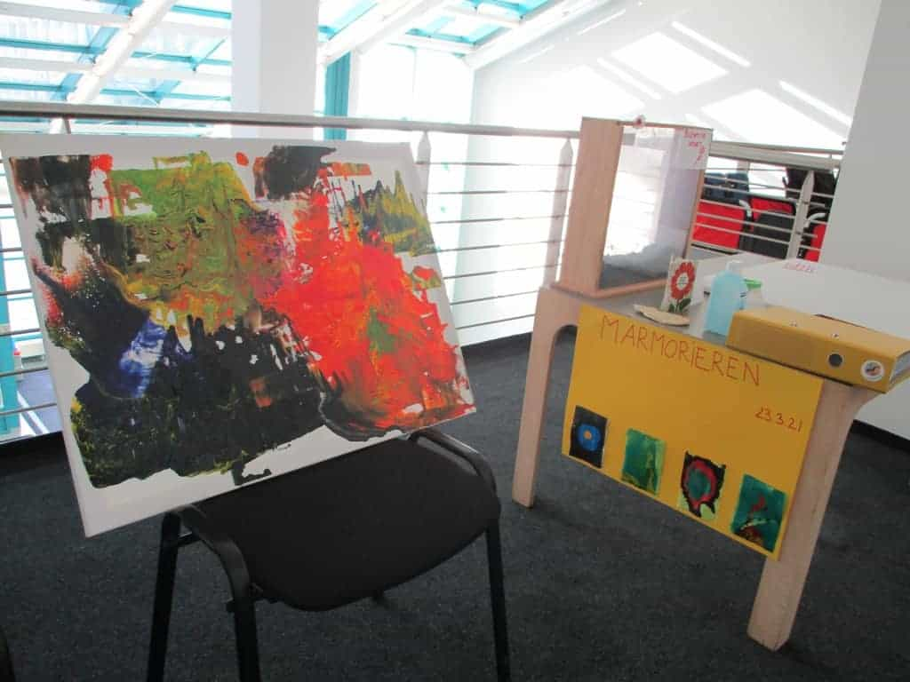 """Auf einem schwarzen Stuhl steht ein buntes Bild mit abstrakter Kunst. Neben dem Stuhl steht ein Tisch an dem ein gelbes Plakat befestigt wurde, af dem """"Marmorieren"""" steht und darunter sind vier bunte Bilder aufgeklebt. Auf dem tisch liegen ein gelber Ordner, eine blaue Desinfektionsflasche und ein Glaskasten, in dem sich Erde befindet."""