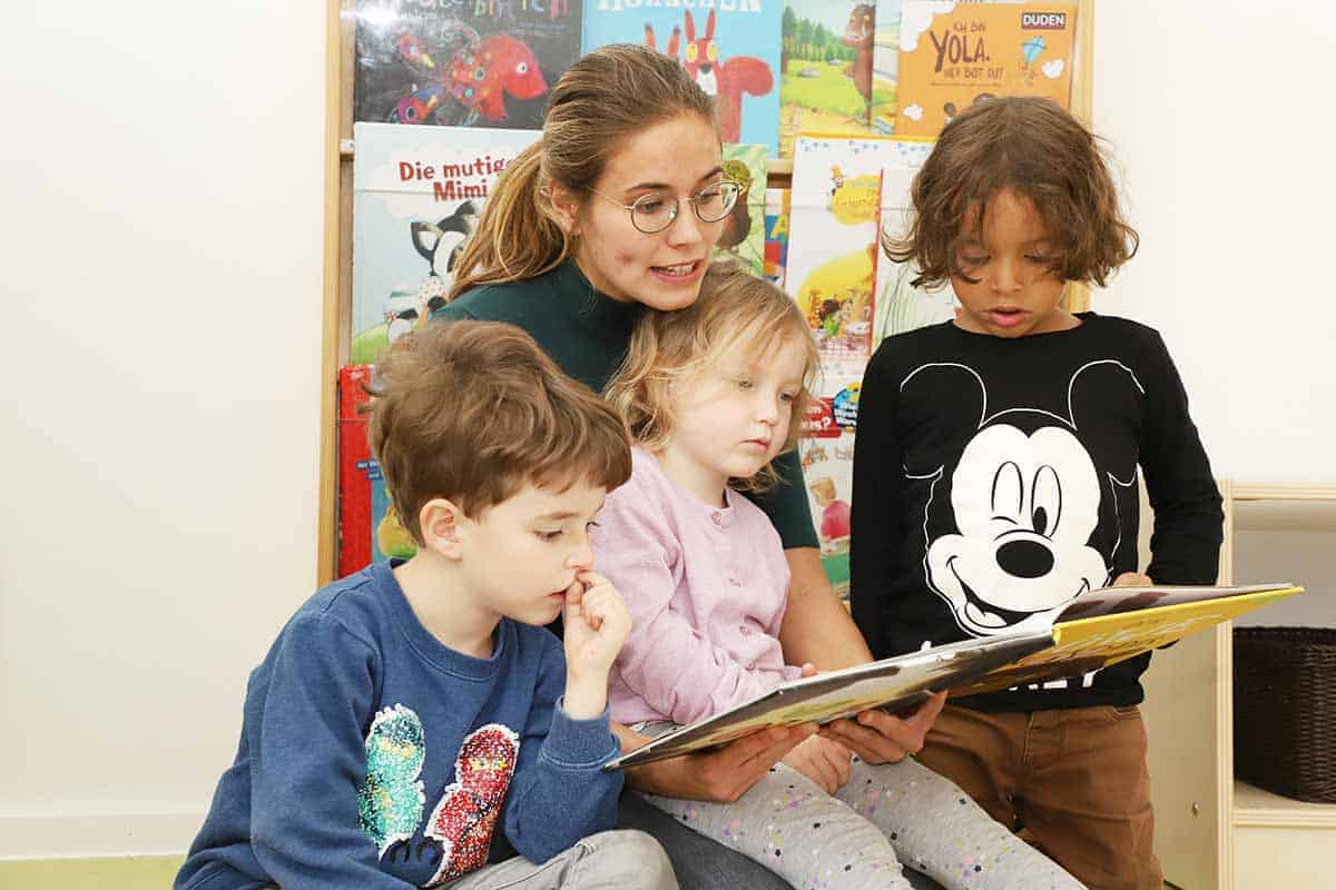 Eine Pädagogin liest ein Buch vor. Ein Mädchen sitzt auf ihrem Schoß, während zwei Jungen daneben stehen.