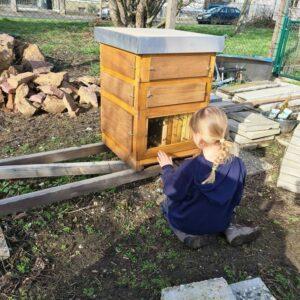 Ein Mädchen sitzt vor einem Bienenhaus.