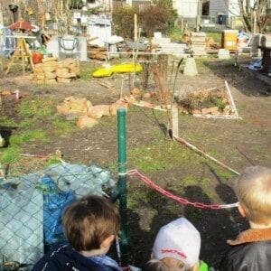 Drei Kinder sehen in einen Garten mit einem Beet, die mit Steinen umrandet sind. Im Garten liegen noch weitere Steine und ein Vogelhaus. Hinter dem Garten stehen zwei Schubkarren und mehrere Steine.