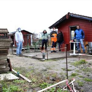Sechs Personen stehen vor abgesteckten Bereichen. Daneben stehen drei Stapel mit Steinplatten. Im Hintergrund steht ein rotes Haus.