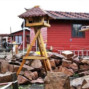 Ein Vogelhaus steht vor einem Steinhaufen. Im Hintergrund steht ein rotes Haus.