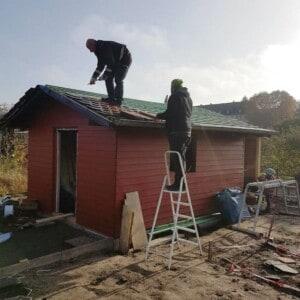 Zwei Männer decken das Dach eines Holzhauses ein. Einer der Männer steht dabei auf einer Leiter.