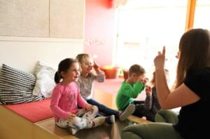 Pädagogin spielt mit kleinen Kindern Fingerspiele