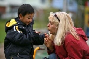blonde Pädagogin pustet kleinem Jungen auf den Finger, auf dem ein Marienkäfer sitzt
