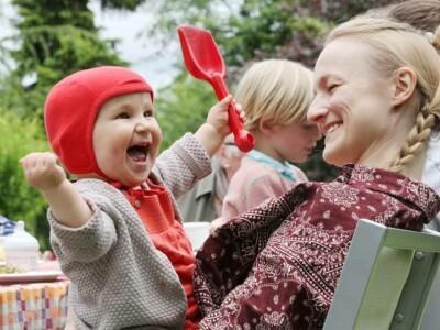 Ein Kleinkind mit roter Mütze sitzt auf dem Schoß seiner blonden Mutter und hebt fröhlich die Arme in die Höhe.