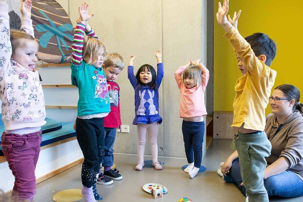 Eine Gruppe Kinder stehen im Kreis, lachen und heben erfreut ihre Arme in die Luft. Eine Erzieherin mit Brille sitzt auf dem Boden.