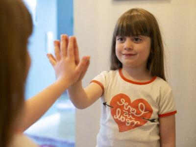Ein braunhaariges Mädchen steht an einem Spiegel, betrachtet sich und streckt die hand in den Spiegel nach ihrem Spiegelbild aus.