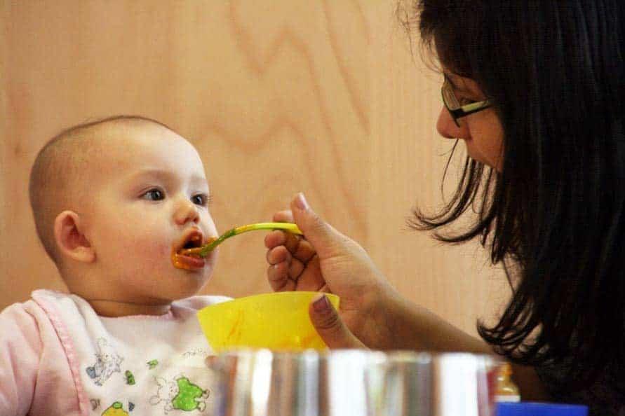 Ein Kleinkind wird von einer FRau mit BRille und dunklen Haaren gefüttert.