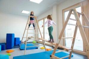 Zwei Mädchen turnen an Holzgerüsten