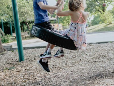 Ein Junge und ein Mädchen schaukeln auf einer Reifen-Schaukel.