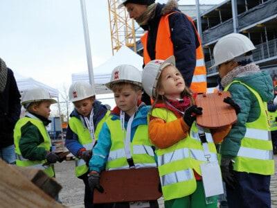 Eine Gruppe KInder mit Bauhelmen steht auf einer Baustelle, ganz vorne ein Mädchen mit einem Ziegel in der Hand.