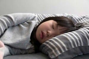 Ein Mädchen liegt mit dem Kopf auf einem Kissen und hat die Augen geschlossen.