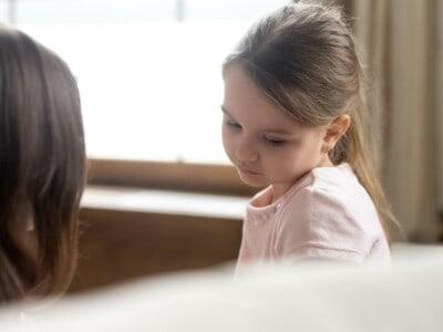 Ein Mädchen mit braunen Haaren und Pferdezopf schaut traurig auf den Boden.
