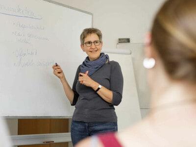 Eine Lehrerin mit Brille steht mit einem Lächeln am Whiteboard / an der Tafel und erklärt etwas.